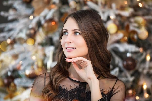 Bella giovane donna felice in bellissimo vestito con trucco e acconciatura nelle decorazioni natalizie
