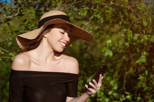 Bella giovane donna felice di etnia caucasica in un cappello di paglia dal sole con tesa larga in un vestito nero con un telefono in mano sorridente in una giornata di sole estivo