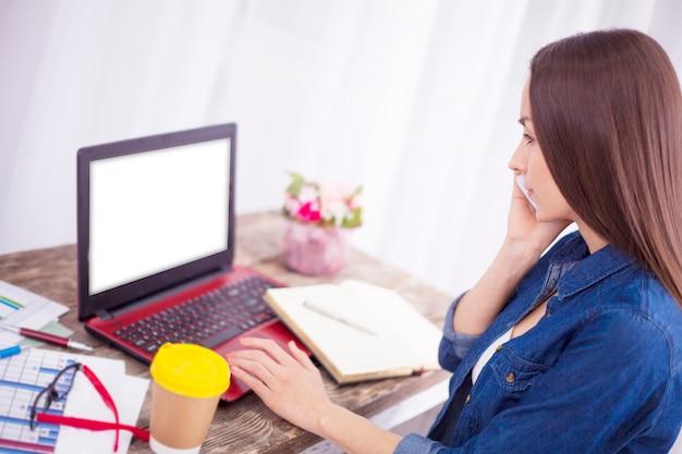Il libero professionista della bella giovane donna felice sta usando un laptop e uno smart phone