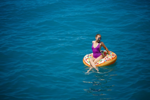 Bella giovane donna felice in costume da bagno con un anello gonfiabile che si rilassa nel mare blu. giornata di sole, vacanza al mare, turismo