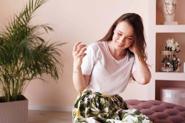 Bella giovane donna felice con la bottiglia di profumo a casa - spogliatoio rosa