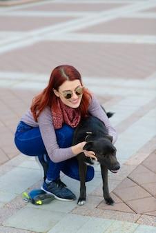 La bella giovane donna felice con il cane nero sveglio si diverte sulla strada. concetto di amicizia tra animali e persone.