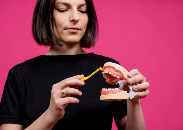Bella giovane donna felice con il singolo spazzolino da denti trapuntato su fondo rosa in bianco