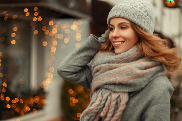 Bella giovane donna felice con un dolce sorriso in maglieria vintage alla moda con un berretto lavorato a maglia e sciarpa che cammina all'aperto durante le vacanze vicino a luci gialle