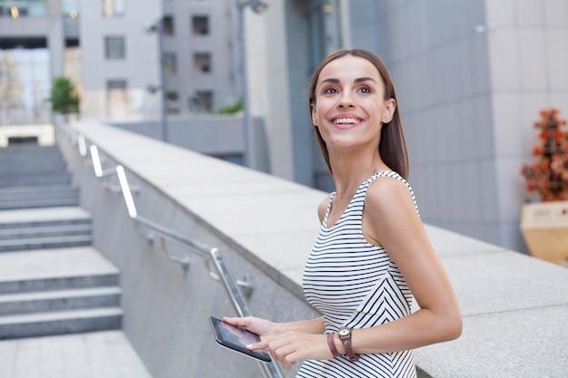 La bella giovane donna felice con una compressa nelle mani distoglie lo sguardo all'aperto