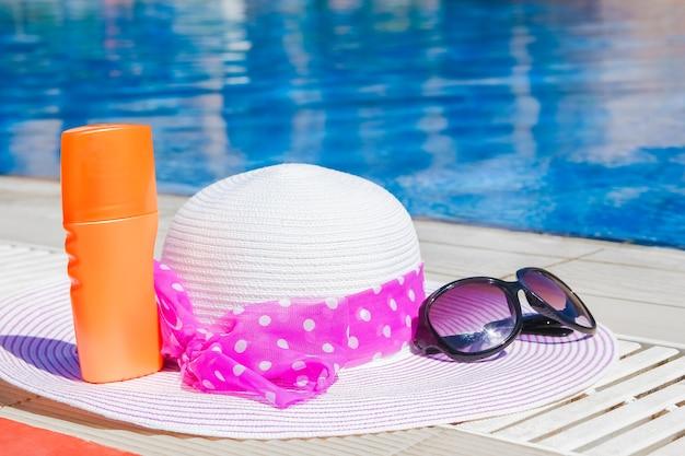 Bellissimo cappello vicino alla piscina con crema e bicchieri