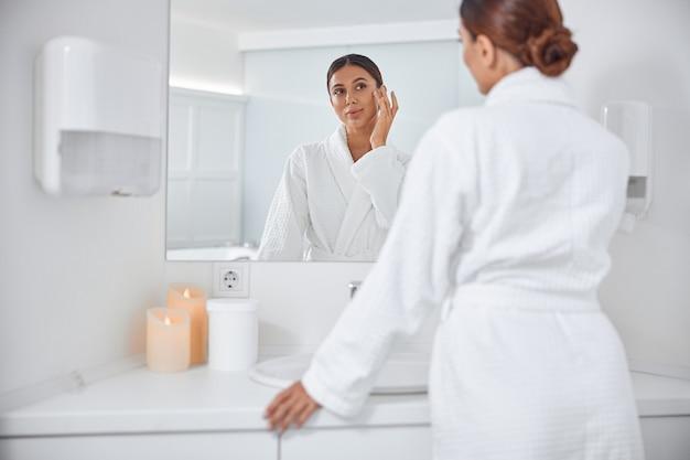 Bella donna caucasica sorridente in buona salute che si prende cura della sua pelle in bagno