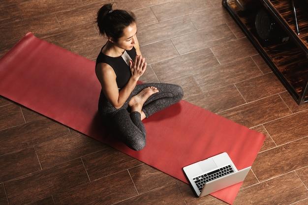 Bella donna in buona salute facendo esercizi di yoga mentre è seduto su un tappetino fitness a casa, utilizzando il computer portatile, stretching