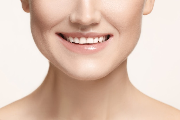 Sorriso di donna bella e sana, primo piano su sfondo bianco