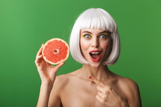 Bella giovane donna in topless in buona salute che indossa i capelli bianchi corti in piedi isolato, mostrando il pompelmo a fette