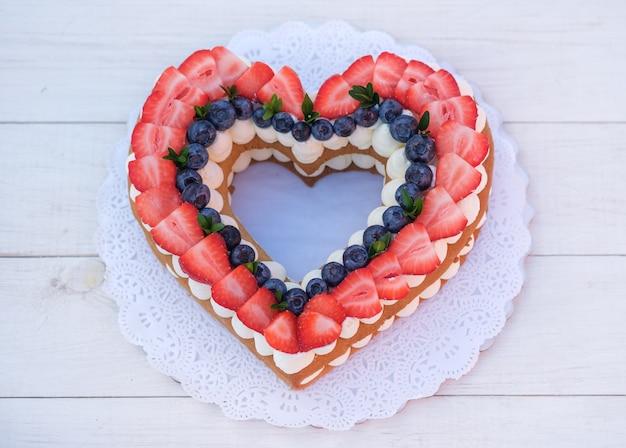 Bella torta a forma di cuore con frutti di bosco freschi per il giorno di san valentino sulla tavola di legno bianca