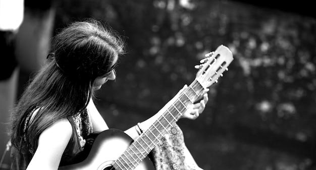 Bella ragazza hippie che suona la chitarra vicino al lago della foresta