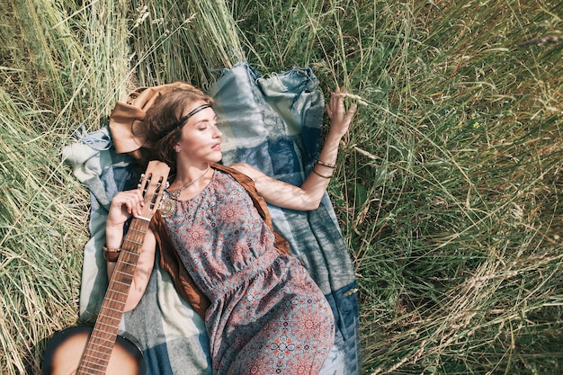 Bella ragazza hippie con la chitarra sdraiato sull'erba falciata