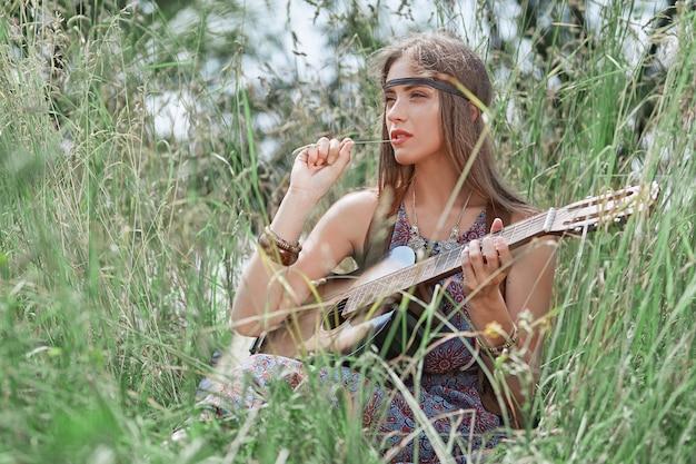 Bella ragazza del hippie con la chitarra che si siede sulla radura della foresta