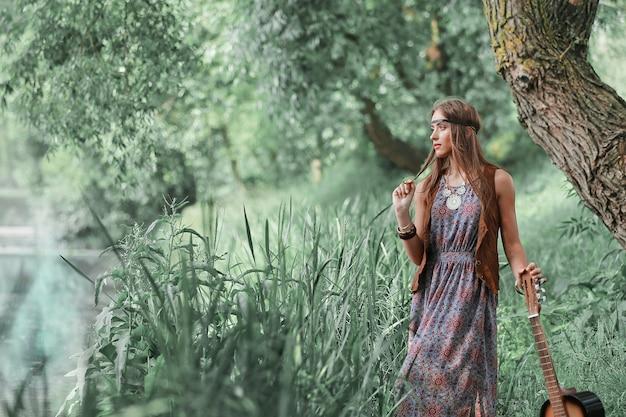 Bella ragazza hippie con una chitarra in piedi vicino a uno stagno nella foresta