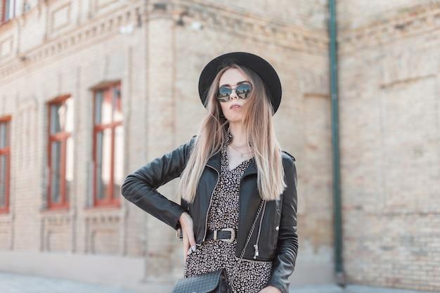 Bella ragazza hipster con occhiali da sole in un vestito alla moda con una giacca di pelle e una borsetta cammina per la città