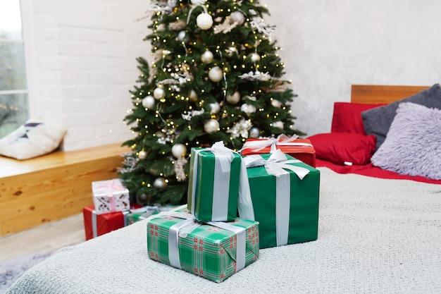 Bella camera decorata con albero di natale e regali sul letto