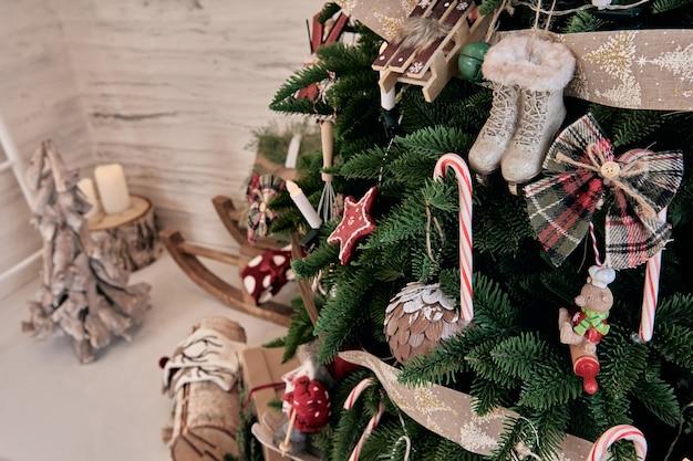 Bella decorazione per la casa fatta a mano fai da te. accogliente stanza decorata con candele e albero di natale con regali sotto. bevanda calda sul tavolo. gli interni di capodanno in uno studio fotografico