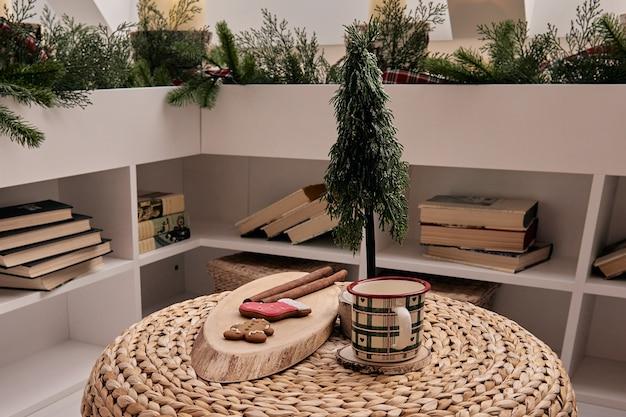Bella decorazione per la casa fatta a mano fai da te. accogliente stanza decorata con albero di natale con regali sotto di esso. bevanda calda sul tavolo. gli interni di capodanno in uno studio fotografico