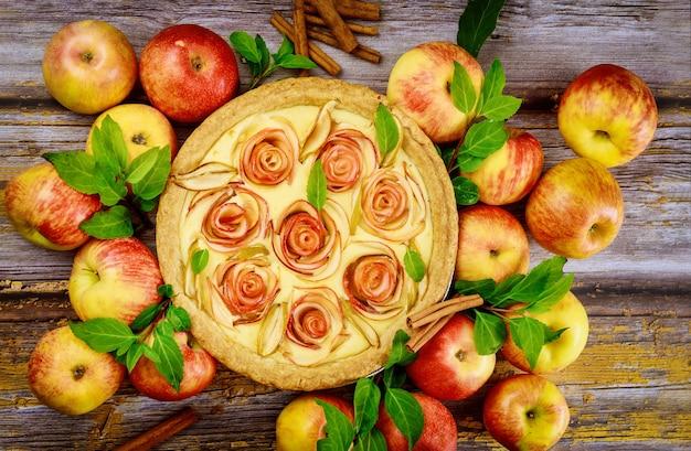 Bella torta di mele fatta in casa e bastoncini di cannella su fondo di legno con mele fresche. vista dall'alto.