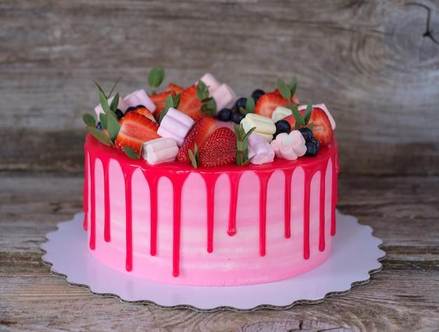 Bellissima torta fatta in casa con crema rosa e rossa, decorata con fragole e marshmallow