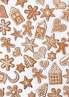 Bellissimi biscotti di pan di zenzero di natale fatti in casa a forma di uomo, stella, cuore, albero, fiocco di neve, casa su bianco. vista dall'alto.