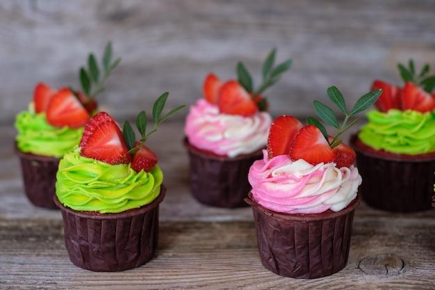 Bellissimi cupcakes fatti in casa con crema di formaggio multicolore, decorata con fragole, su un tavolo di legno