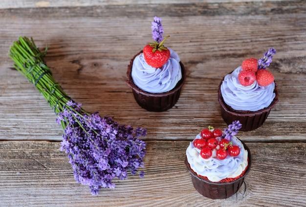 Bellissimi cupcakes fatti in casa con crema di formaggio viola, decorati con bacche di ribes, lampone e fragola e un bouquet di lavanda