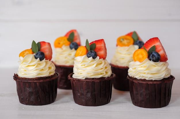 Bellissimi cupcakes fatti in casa con crema di formaggio bianco, fragole e mirtilli sul tavolo bianco