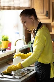 Bella casalinga in guanti di gomma gialli pulizia casa salviette piano di lavoro della cucina utilizzando detergente spray, lava fornelli a induzione con spugna