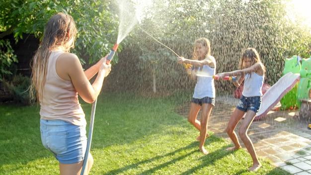 Bella immagine di una famiglia che ride felice con bambini che si divertono in una calda giornata estiva con pistole ad acqua e tubo da giardino. la famiglia gioca e si diverte all'aperto in estate