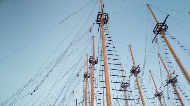 Bella immagine dell'alto albero delle navi e delle barche di legno storiche contro il cielo blu