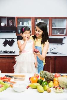 Bella giovane madre e figlia indiane o asiatiche in cucina, con un tavolo pieno di frutta e verdura