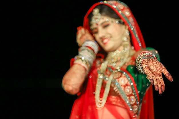 Bella sposa indiana che mostra la mano di mehndi che indossa sari e gioielli d'oro al matrimonio indiano