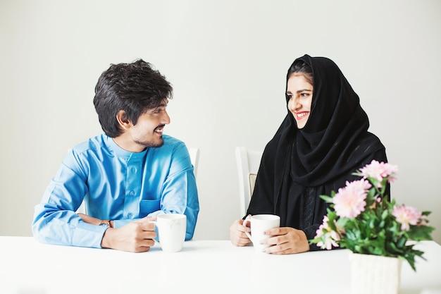 Bella coppia indiana vestita con abiti musulmani che parlano davanti a una tazza di tè