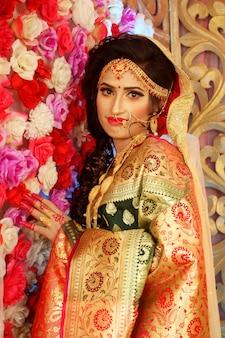 Bella ragazza indiana modello donna indù con abito da sposa e gioielli.