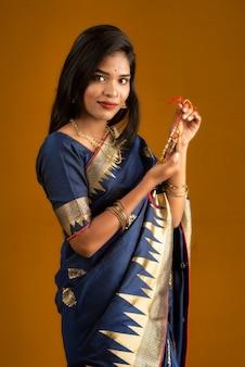 Bella ragazza indiana che mostra rakhis in occasione di raksha bandhan. la sorella lega rakhi come simbolo di amore intenso per suo fratello.