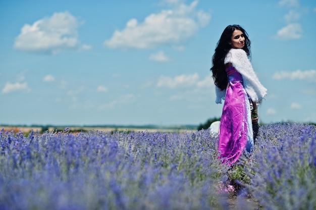 La bella ragazza indiana indossa il vestito tradizionale dall'india di saree nel campo viola della lavanda.