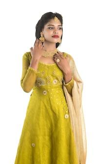 Bella donna tradizionale indiana in posa su bianco.