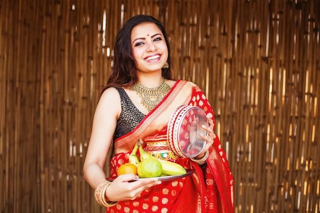 Bella donna indiana in un sari rosso che tiene gli accessori di karva chauth