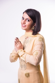 Bella ragazza indiana in abbigliamento etnico in namaskara o posa di preghiera o namaste, in piedi isolato su sfondo bianco