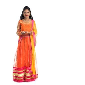 Bella ragazza indiana giovane azienda pooja thali o eseguire il culto su uno sfondo bianco