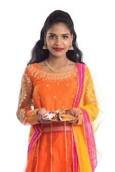 Thali indiano di pooja della tenuta della bella ragazza o culto di esecuzione su una parete bianca