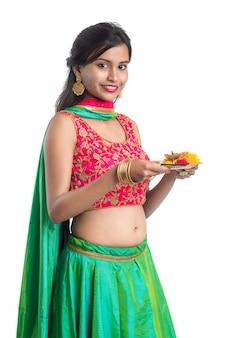 Thali indiano bello di pooja della tenuta della ragazza o culto di esecuzione su un bianco