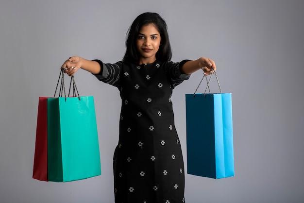 Bella ragazza indiana che tiene e che posa con le borse della spesa su un muro grigio