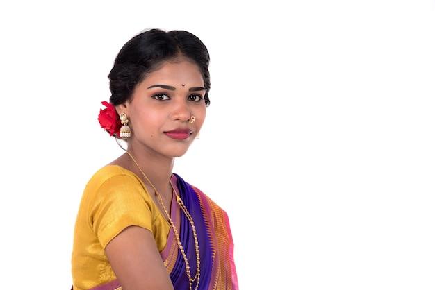 Bella ragazza indiana che posa in saree indiano tradizionale su fondo bianco.