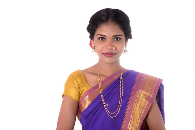 Bella ragazza indiana che posa in saree indiano tradizionale sulla parete bianca