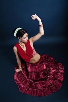 Bella giovane donna indiana che balla in abiti nazionali, danza del tempio