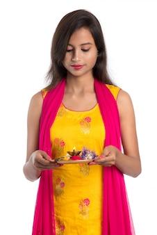 Thali indiano bello di pooja della tenuta della giovane donna o culto di esecuzione su bianco