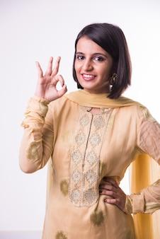 Bella giovane donna indiana in abiti tradizionali che mostra il segno giusto